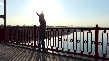özgürlük : Fair-Haired Man Stands And Raises Hands Happily on a Bridge at Sunset in Slo-Mo