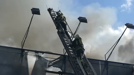 lineman : Two heroes on a metallic staircase extinguish fire with water