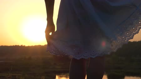 lem : Young Woman Frolics With The Hem of Her White Folk Dress at Sunset in Slo-Mo