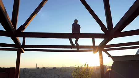dekarz : Blond man sits on a metallic construction at sunset in slo-mo