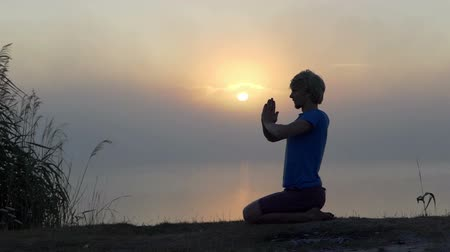 eucharystia : Young man sits and prays on a lake bank at sunset in slo-mo Wideo