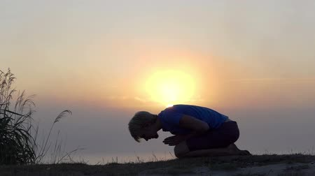 eucharystia : Young man kneels and prays on a lake bank at sunset in slo-mo