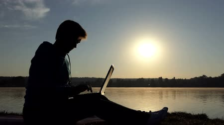 autor : Middle aged woman types her essay on a lake bank