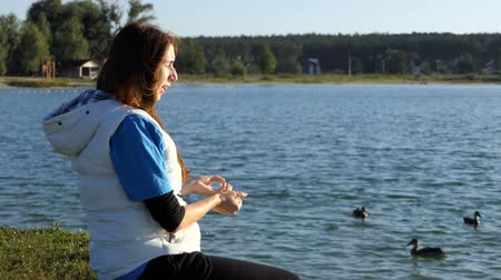 dobrosrdečný : Young woman throws bread to a flock of ducks in a lake