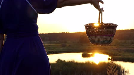 pastry purse : Happy woman rotates a folk basket on a lake bank at sunset in slo-mo
