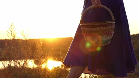 pastry purse : Playful woman goes and rotates a folk basket at sunset in slo-mo