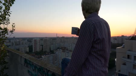 dekarz : 4k - Man drinks tea sits on the top of the building at sunset. Wideo