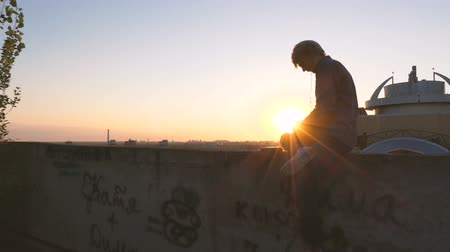 dekarz : Man listening music at sunset on the roof of skyscaper.