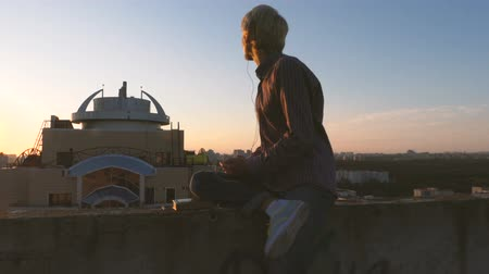 dekarz : Young man sitting on the roof and listening music.