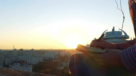 dekarz : 4k - amazing sunset over city and man who listeting music and writing.