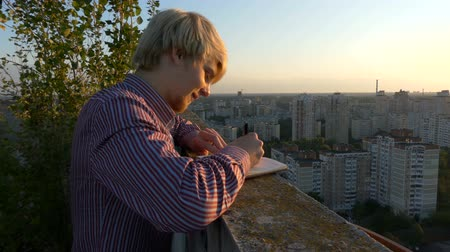 písanka : 4k - Young writer finding his muse on the roof of skyscraper at sunset.