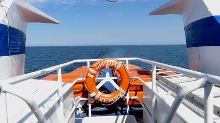lifebuoy : A white ship with a lifebuoy at its stern moves in the sea