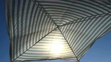 parasol : A striped sunshade on the Black Sea coast in summer Stock Footage