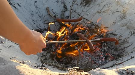 kiełbasa : Three sausages are cooked on the campfire in summer in slo-mo