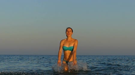 perfect weather : Happy young woman raises her hands and makes splashes in slo-mo
