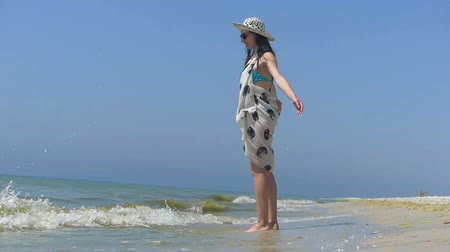 remendo : Young woman in a straw hat and bikini walks on a beach Stock Footage