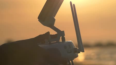 stable fly : Female hands manage the drone control panel at sunset