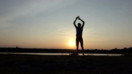 премия : Young man jumps with a champion bowl at sunset in slo-mo