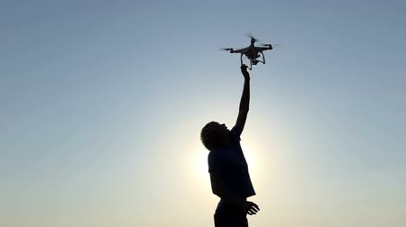 сияющий : Young man tries to touch a flying drone at sunset in slo-mo