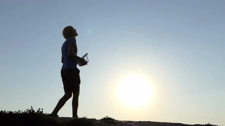 painel : Young man operstes a flying drone with his panel at sunset in slo-mo