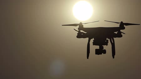 сияющий : A flying drone with four rotating blades at sunset in slo-mo Стоковые видеозаписи