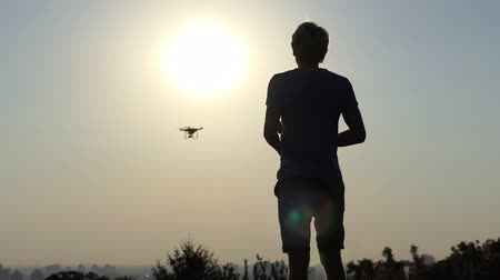 görkemli : Young man operates his modern drone with panel at sunset in slo-mo