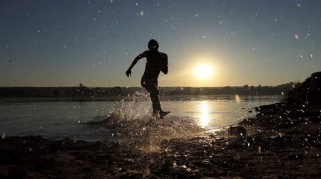 houpačka : Happy young man dances disco in a lake at sunset in slo-mo