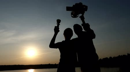 mirrorless : Two young men keeping a stedicam and a champion bowl at sunset