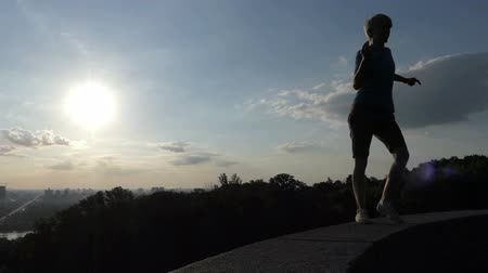 going round : Young man dances on plates covering an embankment wall in Kyiv Stock Footage