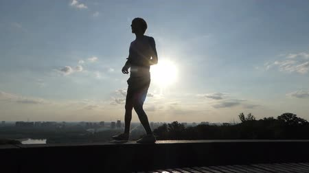 modelo de moda : Happy man dances on plates of an embankment wall in Kyiv in slo-mo Stock Footage
