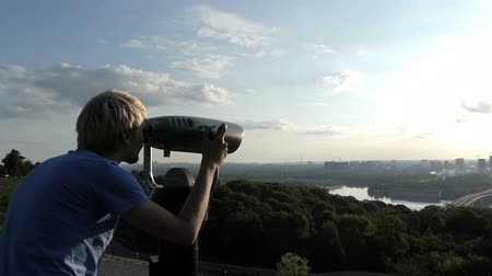 periscope : Young man uses a spyglass on an observation deck over the Dnipro Stock Footage
