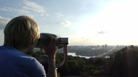 periscope : Smart man uses a spyglass on an observation deck over the Dnipro