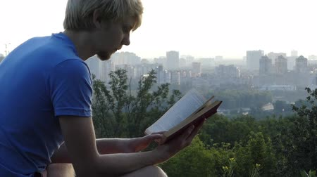 observation deck : Young man reads a book on a curb of an observation deck