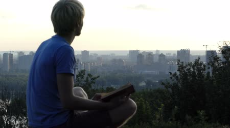 gözlem : Creative man reads a book on the observation deck in Kyiv in slo-mo