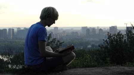 observation deck : Dreaming man reads a book on the observation deck in Kyiv in slo-mo Stock Footage
