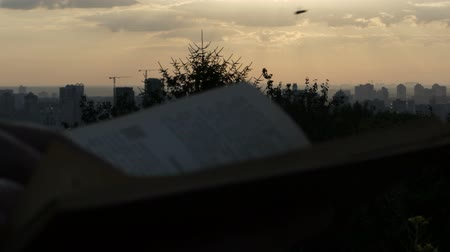observation deck : A pan shot of Kyiv and a book read by a man at sunset in slo-mo Stock Footage