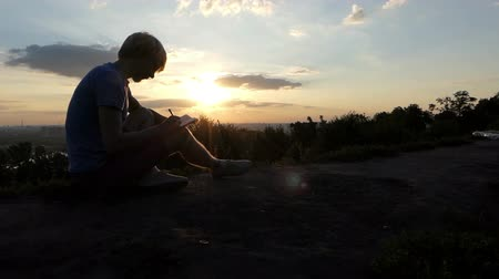 připomínka : Young blogger writes an article on a lawn at sunset in slo-mo