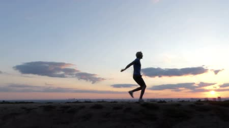 paleta : Blond man runs and jumps on a lawn at sunset in slo-mo