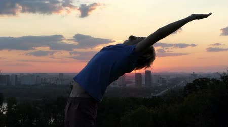 elevação : Sportive man raises hands and spans his back at sunset in slo-mo Stock Footage