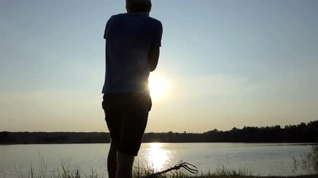 atirar : Young man tries to shoot a golden sunpath at sunset in slo-mo