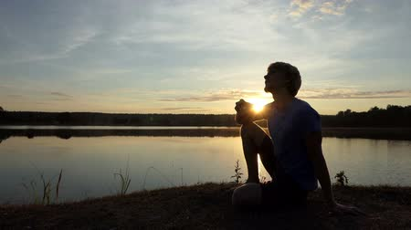 napoje : Happy man drinks tea sitting on a lake bank at sunset in slo-mo
