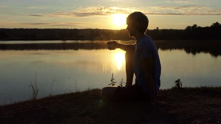 optimistický : Dreaming man drinks tea sitting on a lake bank at sunset in slo-mo