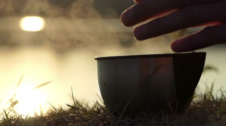 paleta : Metallic cup of tea is placed on a lake bank at sunset in slo-mo