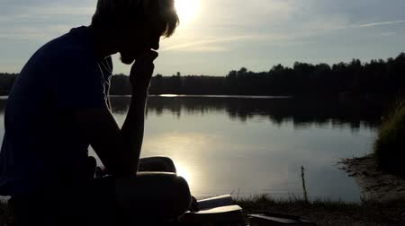 istif : Smart man reads a book on a lake bank at sunset in slo-mo