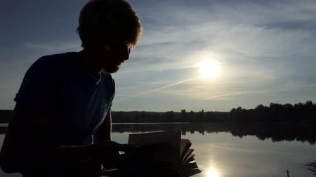 orar : C-student looks through his book on a lake bank in slo-mo