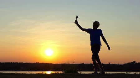 raises : Sportive man raises his winner bowl happily at a lake in slo-mo