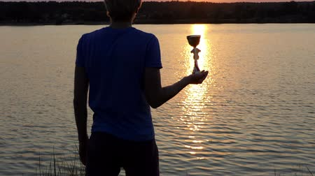 paleta : Young man keeps his winner bowl on a sunpath at a lake