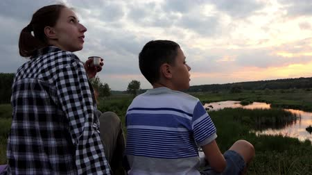 lenyűgözött : Young woman and a boy look at sky with their drone at a lake