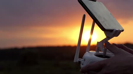 pervane : Womans hands keep a control panel to operate a drone at sunset