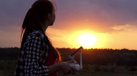 golden color : Smart woman operates a panel to control a drone at sunset